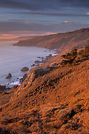 Sunset light over the coastal cliffs above the Pacific Ocean, from Muir Beach Overlook, Marin County, California Sunset light on the rugged coastal cliffs overlooking the Pacific Ocean from above Muir Beach, Marin County, California