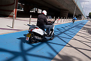 A male moped rider follows a woman cyclist, illegally riding on the dedicated cycle path that travels alongside the elevated section of the A13 Newham Way in Canning Town in the East End, on 11th August 2021, in London, England.