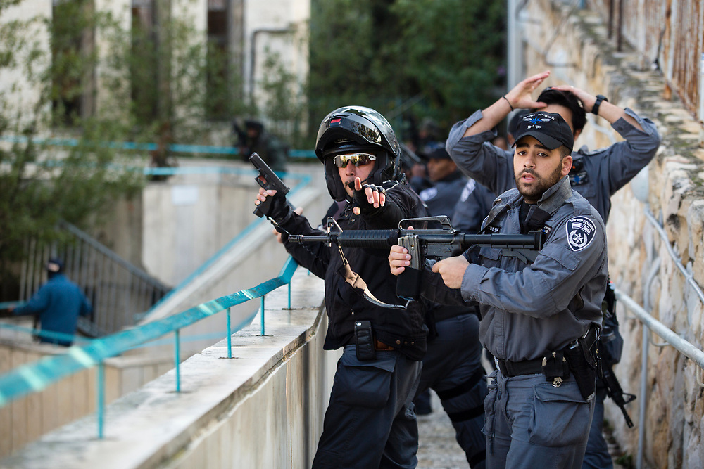 Israeli policemen take position near the scene of an attack in a Synagogue in Jerusalem, Israel, on November 18, 2014. Two Palestinian men armed with axes, knives and guns  attacked worshippers praying inside the Synagogue, killing four people being shot dead by police, Israeli officials said.