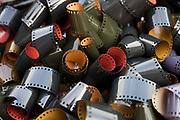 An aerial detail of many coils of undeveloped, generic 35mm film emulsion, collected before disposal. Film is an antiquated analogue technology that has been largely replaced by the remarkable digital mega pixel camera and the process of recording photographic images and their safe-keeping is fast-becoming lost as a skill. The square holes to the top and bottom are for the camera winder to grasp on to, allowing the film to advance to the next frame inside the light-tight camera body. This film is unprocessed, having been removed from its cassette for display.