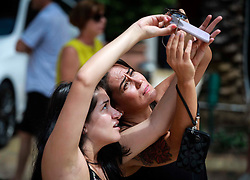 August 21, 2017 - Florida, U.S. - Laura Goez (left) of West Palm Beach and Lina Toledo of Colombia try to shade the lens of a smartphone camera with a pair of sunglasses to take a photo of the eclipse at CityPlace in West Palm Beach Monday, August 21, 2017. (Credit Image: © Bruce R. Bennett/The Palm Beach Post via ZUMA Wire)