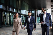Businessmen and woman walking past corporate offices in the commercial and financial centre of St Helier, Jersey, CI