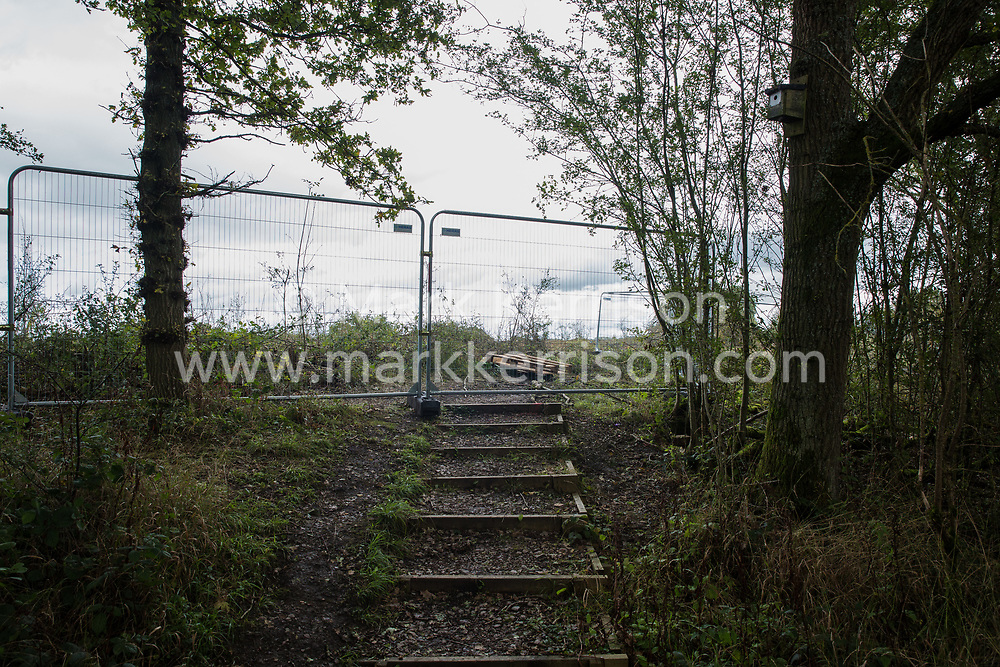 Calvert, UK. 6th October, 2020. A footpath leading towards an area of Calvert Jubilee nature reserve cleared of trees and vegetation by contractors working on behalf of HS2 Ltd. HS2 Ltd seized possession of the eastern side of the nature reserve, which is maintained by the Berks, Bucks and Oxon Wildlife Trust (BBOWT) and is home to bittern, breeding tern and some of the UK's rarest butterflies, on 22nd September in order to carry out clearance works in connection with the HS2 high-speed rail link.