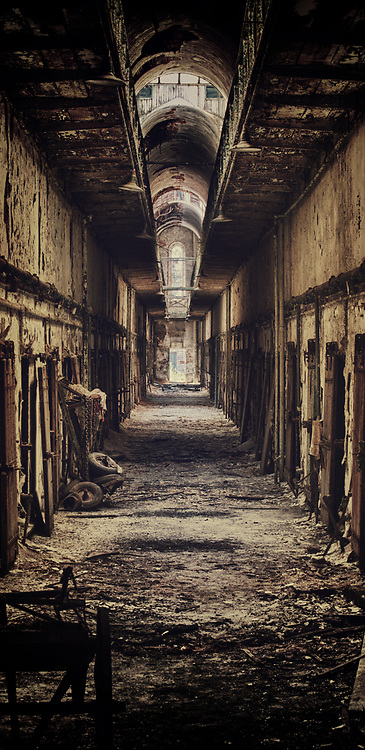 """Eastern State Penitentiary was once the most famous and expensive prison in the world, but stands today in ruin, a haunting world of crumbling cellblocks and empty guard towers. Its vaulted, sky-lit cells once held many of America's most notorious lawbreakers, including """"Slick Willie"""" Sutton and """"Scarface"""" Al Capone."""