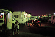 """Manouche camping site, at night,  on the outskirts of Saintes Maries de la Mer<br /><br />""""Le Pelerinage des Gitans""""; the French gypsy pilgrimage of Saintes Maries de la Mer, Camargue, France<br /><br />Sainte Sara is an uncannonized saint, who legend says looked after the Christian Saints Marie Jacobe and Marie Salome, cousins of Mary Magdalene, who arrived, it is said, on the shores of the Camargue in a rudderless boat. Saint Sara is the patron saint of gypsies who come from far and wide to see her. There are even paintings of Sara as 'Kali' the black saint in Eastern Europe. Sara may have been the priestess of 'Ra' the sun-god or even servant girl to the Christian saints. No-one really knows.<br /><br />For a few weeks of the year, Roma, Gitan and Manouche gypsies come from all over Europe in May, camping in caravans around Saintes Maries de la Mer. It is a festive time where they play music, dance, party and christen their children. They all go to see Saint Sara in the crypt, kissing or touching her forehead. Many put robes on her shoulders, making her fat for the procession. In the main Gypsy procession of the 24th May, Saint Sara is allowed to leave her crypt, beneath the church, and is carried from the church to the shores of the mediterranean and back again. One day a year she is free from her prison. Hundred's of years ago the Gypsies used not even to be allowed into the church, only into the crypt like Sara...<br /><br />Roma gypsies still suffer oppressive prejudice and racism and are one of the ethnic groups the most persecuted and marginalised across Europe. The festival is one of the times where they celebrate with people of all races, their faith and traditions"""