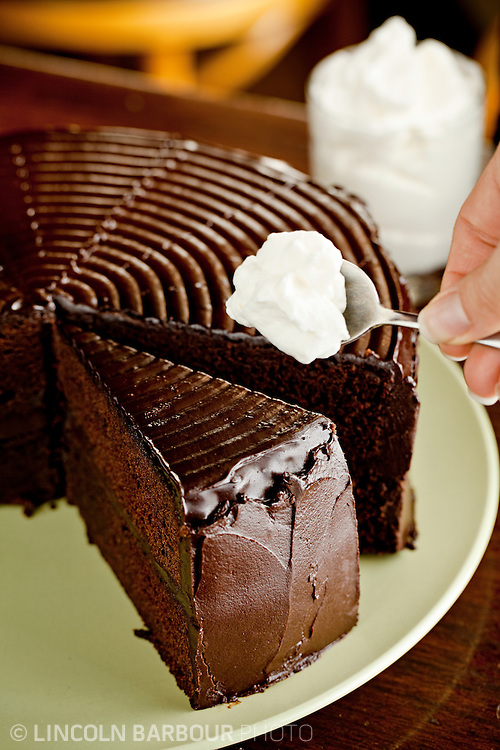 A delicious looking piece of chocolate cake is about to be adorned with a spoonful of homemade whipped cream.
