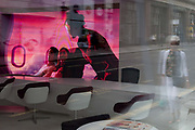 A ladys face is obscured as she walks past a Qatar Airways travel agencys video loop, seen through its window in Mayfair, on 15th July 2019, in London, England.