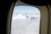cloud forming large mountains seen from the airplane while flying above the clouds