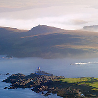 Valentia Island Lighthouse and Begenish Island during misty Sunrise with fisher boat / vl106