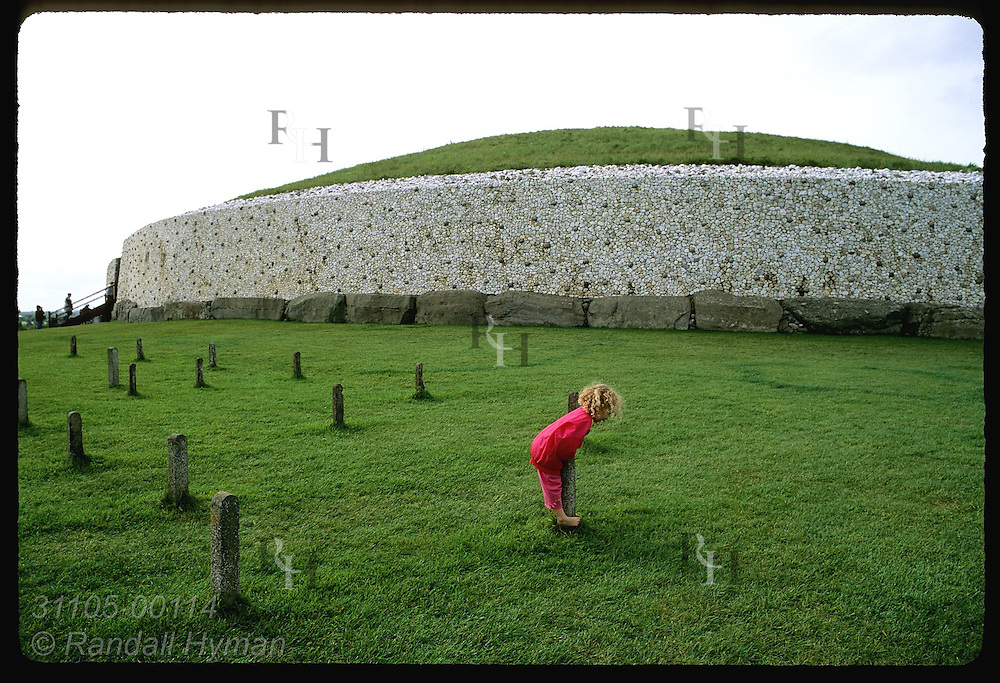 Child plays on concrete posts in front of Newgrange, a Neolithic (3200 BC) passage grave in Boyne Valley; County Meath, Ireland.