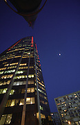 The Tour Montparnasse skyscraper office building at night with moon. Paris, France.