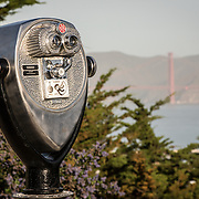Lookout binoculars, with the Golden Gate Bridge in the background, as seen from Coit Tower on top of Telegraph Hill in San Francisco, California. The tower was built in 1933 from funds bequeathed by Lillie Hitchcocl Coit.