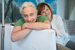 Portrait of couple sitting on couch in living room, smiling