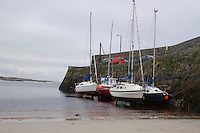 Boats moored at the pier in Spiddle County Galway Ireland at low tide