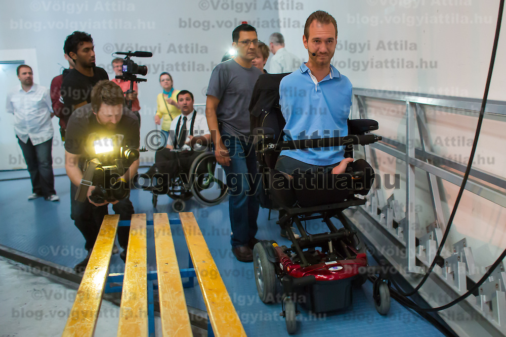 Nick Vujicic (R) born without legs and arms prepares his speech about hope in Budapest, Hungary on April 18, 2013. ATTILA VOLGYI