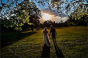 A bride and groom walk in a large field during their wedding in Asbury Park, New Jersey.