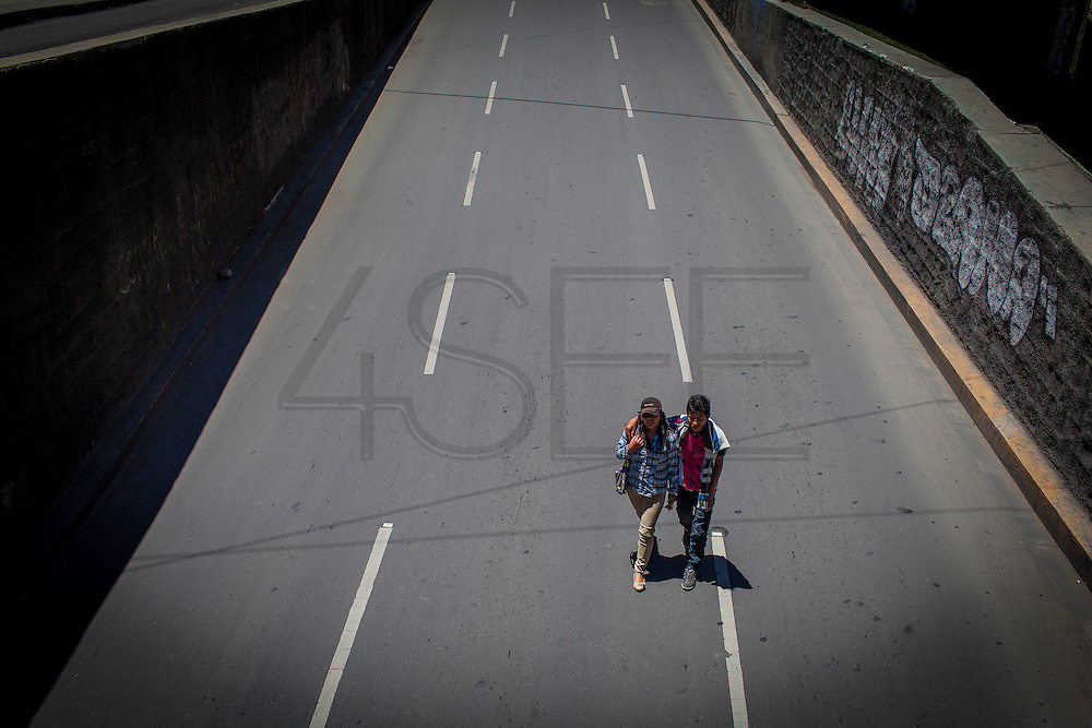 A couple walk in the middle of the road that leads to the tunnel below the Plaze Bicentenario, La Paz. Due to Government restrictions almost any vehicles could circulate on the streets of the city, leaving them to the people. Such sanctions turn La Paz into an almost ghost town. During elections period in  Bolivia, the country faces several restrictions, like no alcohol for sale 48 hours before and 12 after the election; no public gatherings, shows of any kind until the political parties made their speeches on the election night; its completely forbidden the circulation of any vehicles, private or governmental except with the permit from the Electoral Tribunal, which means it would be basically no cars, buses or anything circulating in the city; no long distance buses, the terminal will be close from Saturday until Monday and even flights will not be allowed except the ones leaving the country or the international ones doing stop-over. It is a completely shut down of the country.