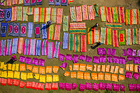 Aerial view of people working in a public laundry draining and drying colourful clothes at sunlight, Araihazar, Dhaka province, Bangladesh.
