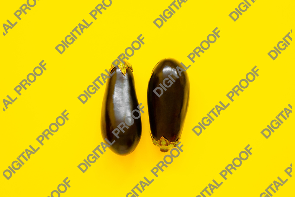 Pair of aubergines isolated in yellow background viewed from above - flatlay look
