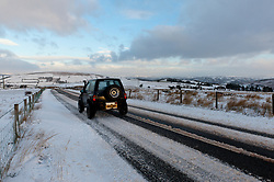 © Licensed to London News Pictures. 13/01/2017. Builth Wells, Powys, Wales, UK.  Vehicles negotiate the B4520 in a wintry landscape between Brecon and Builth Wells on the high moorland of the Mynydd Epynt range in Powys, Wales, UK. Photo credit: Graham M. Lawrence/LNP