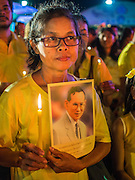 05 DECEMBER 2014 - BANGKOK, THAILAND: A woman holds a candle and picture of Bhumibol Adulyadej, the King of Thailand, during birthday celebrations for the King. Thais marked the the King's 87th birthday Friday. The King was born on December 5, 1927, in Cambridge, Massachusetts. The family was in the United States because his father, Prince Mahidol, was studying Public Health at Harvard University. He has reigned since 1946 and is the world's currently reigning longest serving monarch and the longest serving monarch in Thai history. Bhumibol, who is in poor health, is revered by the Thai people. His birthday is a national holiday and is also celebrated as Father's Day. He is currently hospitalized in Siriraj Hospital, recovering from a series of health setbacks.     PHOTO BY JACK KURTZ