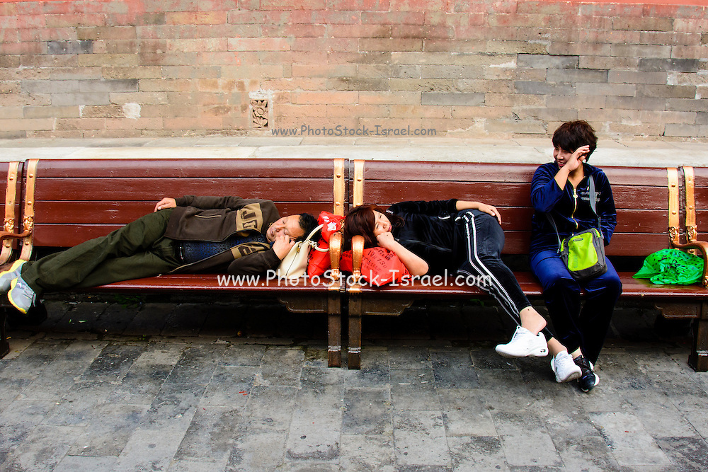 China Beijing, Chinese travellers resting on a bench