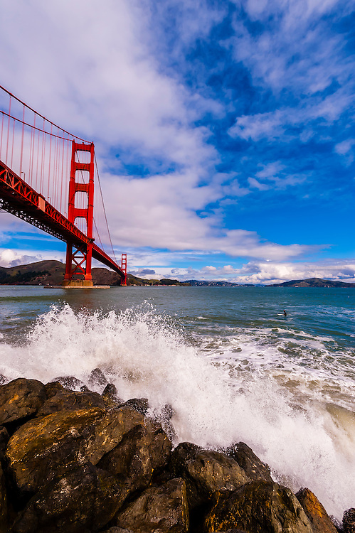 Waves crashing against the rocks at Fort Point (Golden Gate Bridge in background), San Francisco, California USA