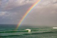 Rainbow arcs over big swell, Duranbah, Gold Coast, Queensland, Australia