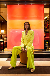 """© Licensed to London News Pictures. 19/05/2021. LONDON, UK. British abstract artist Nat Bowen' poses with her work 'Love Bubble', 2020. Preview of """"Chromadelic"""", Nat Bowen's solo exhibition at 45 Park Lane in Mayfair. The artist uses the study of Chromology, the psychology behind colour, taking influences from the colours and shapes of the 60s and 70s, to layer resin pigmented with bright neon colours against rare natural pigments.  The highlight is the 'Pink Diamond' with natural rose petal pigment and genuine pink diamond dust set within 69 layers of resin.  Her show runs until 28 June 2021.  Photo credit: Stephen Chung/LNP"""