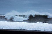 Dramatic dangerous waves of Atlantic Ocean onto black volcanic sand beach Reynisfjara near the village Vík i Myrdal, South Iceland