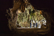 Tourists explore Nok Aen cave which is part of the Vieng Xay Caves in Vieng Xay District, Houaphanh Province, Laos, Southeast Asia. Also called the 'Hidden City,' the caves served as the Pathet Lao revolutionary movement's command center from 1964 to 1975, housing some 20 000 people and contained government offices, temples, markets, schools, hospitals, theaters and factories.