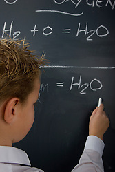 Back view of a school boy writing on a blackboard
