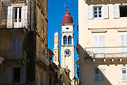 Street scene by Spianada and Church of Saint Spyridon with traditional clock belltower in Kerkyra, Corfu Town, Greece