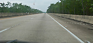 US 90 4-lane highway barrier and swamp forest view obstructed by barrier