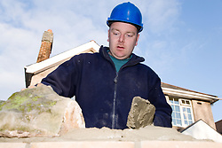 Builder cementing a brick wall,