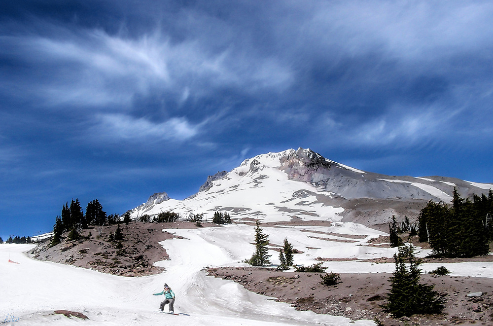 A snowboarder at the top of Mt. Hood under a bright blue sky with wispy clouds.