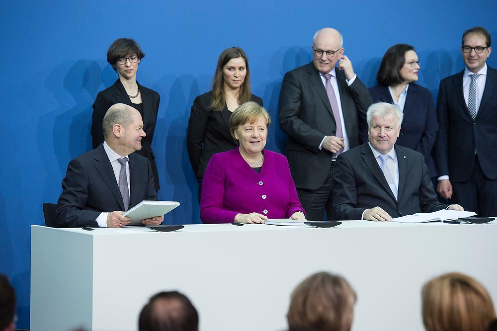 12 MAR 2018, BERLIN/GERMANY:<br /> Horst Seehofer (L), CSU, desig. Bundesinnenminister, Angela Merkel (M), CDU, Bundeskanzlerin, und Olaf Scholz (R), SPD, desig. Bundesfinanzminister, in der zweiten Reihe: zwei Damen des Protokolls, Volker Kauder, CDU, CDU/CSU Fraktionsvorsitzender, Andrea Nahles, SPD Fraktionsvorsitzende, Alexander Dobrindt, Vorsitzender der CSU Landesgruppe, Unterzeichnung des Koalitionsvertrages der CDU/CSU und SPD, Paul-Loebe-Haus, Deutscher Bundestag<br /> IMAGE: 20180312-02-017