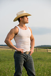 cowboy in a tank top outdoors on a ranch