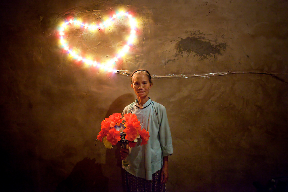 Lu Deqing stands in front of a heart-shaped light her youngest son put up before leaving the village to find work in the city. Both her sons are migrant laborers; one is a tofu seller and the other a porter. They tell their parents that they neither make enough money to help them financially, nor enough to visit them during Chinese New Year. Lu misses her sons terribly and wishes daily for them to come home and get married.