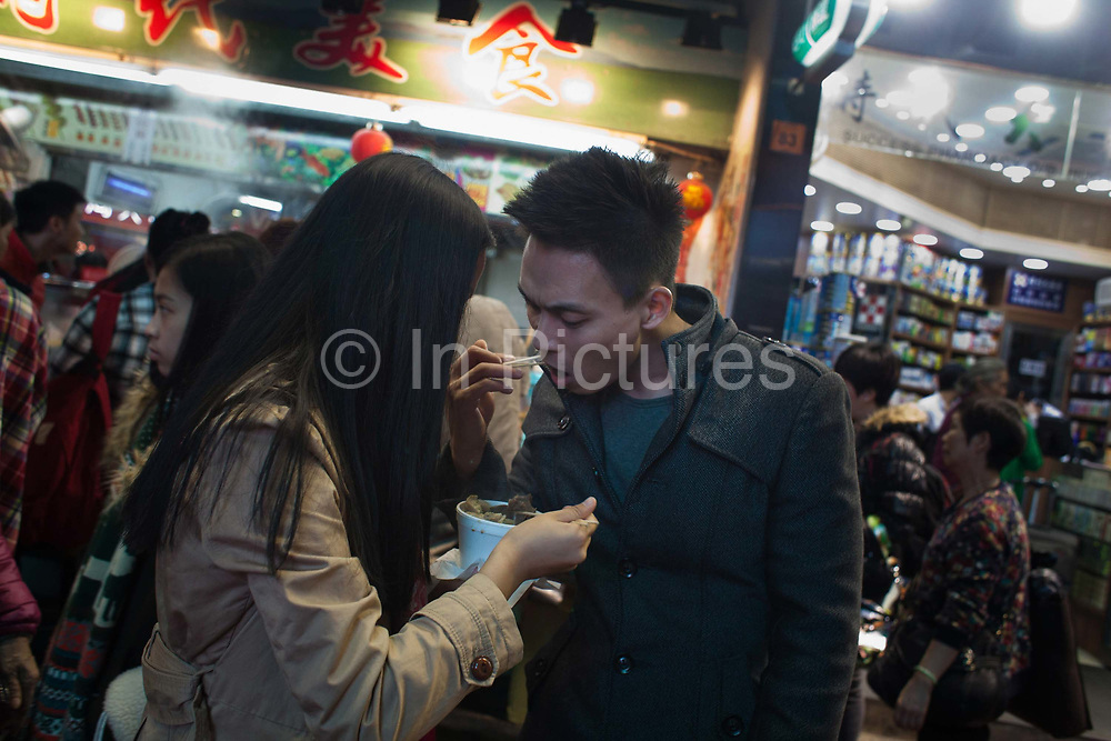 A young smart couple eat street food using chopsticks in Times Square at Christmas time.  7 million people live on 1,104km square, making it Hong Kong the most vertical city in the world.