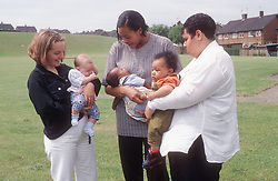 Multiracial group of teenage mothers holding babies,