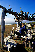 Image of a woman sitting on a driftwood bench overlooking the Pacific Ocean in Yachats, Oregon, Pacific Northwest, model and property released by Andrea Wells