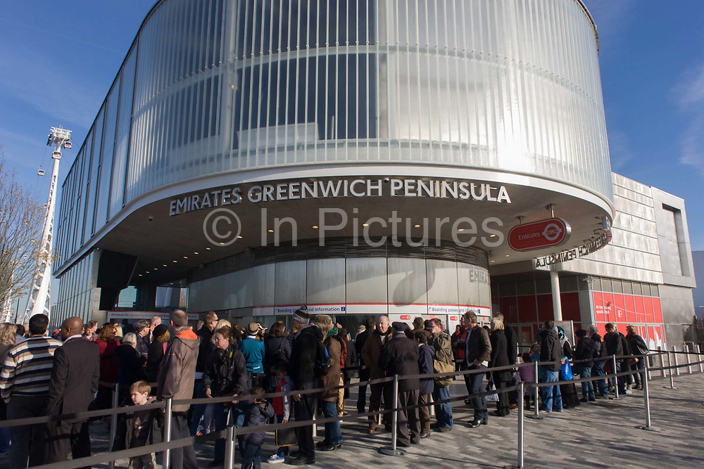 Passengers queue at the southern Greenwich Peninsular terminus of the (Emirates) Thames Cable Car, London. <br /> There are 34 gondolas, each with a maximum capacity of 10 passengers. The Emirates Air Line (also known as the Thames cable car) is a cable car link across the River Thames in London built with sponsorship from the airline Emirates. The service opened on 28 June 2012 and is operated by Transport for London. The service, announced in July 2010 and estimated to cost £60 million, comprises a 1-kilometre (0.62 mi) gondola line that crosses the Thames from the Greenwich Peninsula to the Royal Docks.
