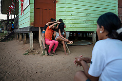 NO WEB/NO APPS - Exclusive. (Text available) A group of girls are combing each other's hair, in 'Palma Real' native community, near Puerto Maldonado, Peru on July 17, 2017. The Amazon rainforest is famous as 'The Lung of the Earth', but also for the presence of numerous native communities, who have always lived isolated and in close contact with nature for generations, used to seek for food and medicines and to build items directly from the environment in which they live. The unstoppable rise of globalization has drastically changed their needs, expectations and consequently their way of life. Located in the Tambopata National Reserve, on the border between Peru and Bolivia, the native Comunidad Palma Real is one of the clearest examples of this change. Living on the banks of the Madre de Dios River since approximately 1976, Palma Real comprises about 300 people part of the nomadic community Ese-Eja, established in the Amazon rainforest of Peru before the Spanish colonization. Photo by Giacomo d'Orlando/ABACAPRESS.COM