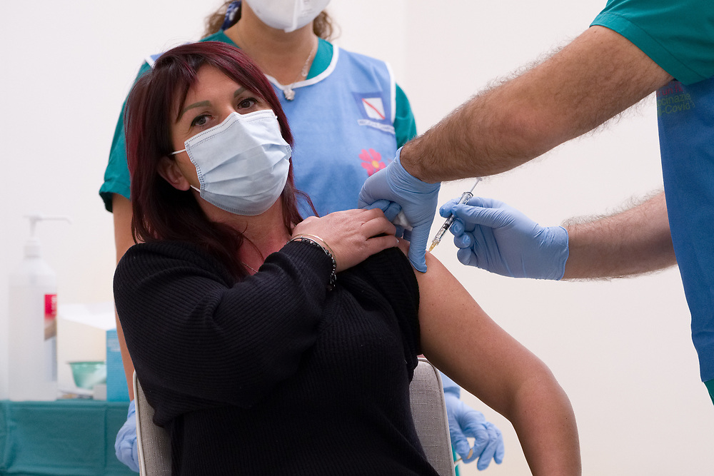 A woman wearing a protective face mask against the spread of COVID-19 coronavirus receives a dose of the Pfizer-BioNTech COVID-19 vaccine at Ospedale del Mare in Naples, southern Italy, on December 27, 2020. Today is started the vaccination campaign simultaneously throughout Europe.