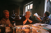 Foire Gras and dairy farming family's women experience hardships together during breakfast at their home in Alsace. ..The Kesslers live on the farm in the quiet village of Boofzheim in Alsace, France. Their business is producing Foie Gras and they raise force-fed ducks near the German border region. The youngest member is daughter Mireille wearing a blood-stained apron. She is about to cut the throat of a duck, draining the body and especially the liver of blood. After tapping the head with a knife to render the animal unconscious, she stands in a pool of  blood from other birds which stains the courtyard floor. On the left, her parents and grandmother are plucking the feathers from newly-killed carcasses which are strung up on a special rack for this purpose. France produces and consumes the most Foie Gras in Europe using the French Gavage method of forcing ducks or geese to consume vast quatities of corn mash down the esophagus two weeks before slaughter.