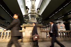 Businessmen walking across historic Nihonbashi Bridge in central Tokyo Japan
