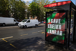 London, UK. 15th May, 2021. Save Sheikh Jarrah artwork by Protest Stencil is pictured at a bus shelter in London on Nakba Day in protest against Israeli attempts to forcibly displace Palestinian families from the Sheikh Jarrah neighbourhood of East Jerusalem where they have lived for many decades.