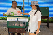 03 MARCH 2013 - BANGKOK, THAILAND: <br /> A woman drops her completed ballot into the ballot box at a polling place in Benchasiri Park in Bangkok. Bangkok residents went to the polls Sunday to elect a new governor. Voter turnout was expected to be heavy for a local election. Pongsapat Pongchareon, the Pheu Thai candidate is thought to hold a slight lead over Sukhumbhand Paribatra, the Democrats' candidate. There are a total of 25 candidates in the election but only Pheu Thai and the Democrats are given a chance of winning.     PHOTO BY JACK KURTZ