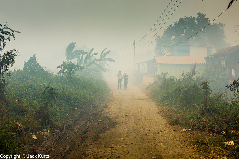 17 MARCH 2014 - PHRAEKSA, SAMUT PRAKAN, THAILAND:    People walk through smoke out a landfill in Samut Prakan province. A fire apparently spontaneously started in the landfill in Samut Prakan over the weekend and threatens the homes of workers who live near the landfill. The fire Officials said the fire started when garbage in the landfill burst into flames and the flames were spread by hot, dry winds. Hundreds of people have been evacuated because of the fire and acrid smoke from the fire has spread as far as Bangkok. It hasn't rained in central Thailand in more than three months, impacting agriculture and domestic water use. Many farms are running short of irrigration water and salt water from the Gulf of Siam has come up the Chao Phraya River and infiltrated the water plants in Pathum Thani province that serve Bangkok.  PHOTO BY JACK KURTZ